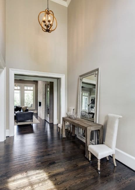 This foyer features a hardwood flooring, white walls and a small chandelier set on a high ceiling.