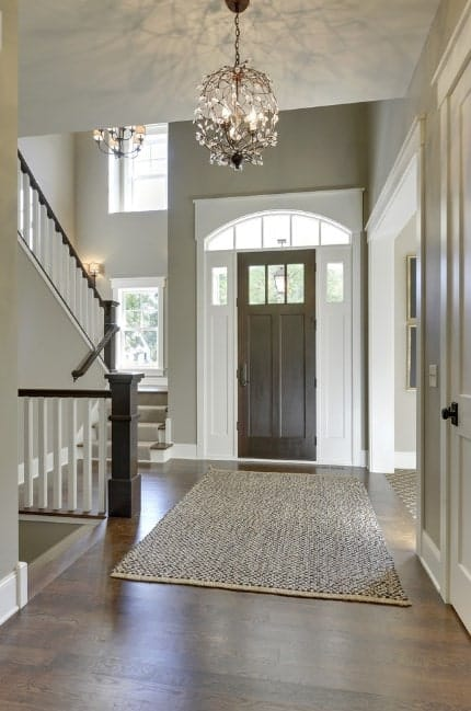 Foyer with a hardwood flooring and a rug, along with gray walls lighted by a charming chandelier.