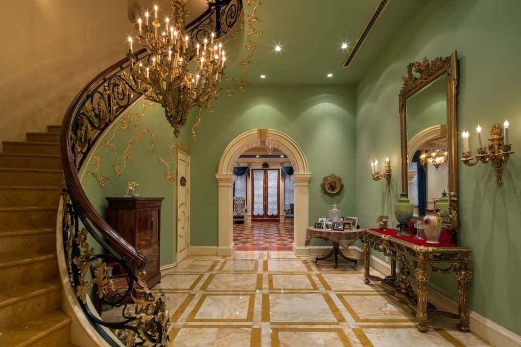 This magnificent foyer is just magical. The flooring looks classy along with the green walls with a set of wall lighting. The staircase matches the elegant chandelier.