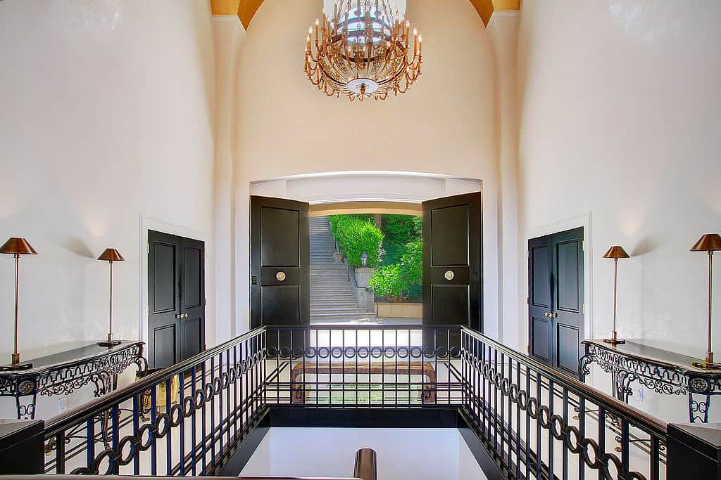 This modish foyer features sparkling flooring and white walls lighted by an enchanting chandelier set on a archway ceiling.
