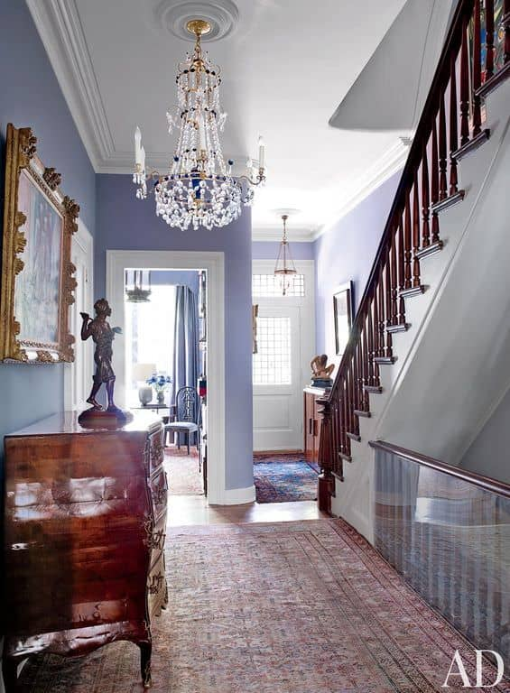Small foyer featuring a large rug set on a vinyl flooring lighted by a grand chandelier.