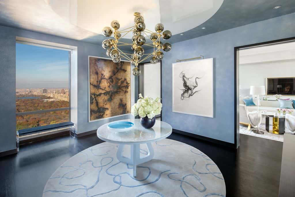 This foyer boasts a combination of lovely blue walls with enchanting wall decors together with a dark hardwood flooring topped by a beautiful rug. Just above the center table is the eye-catching chandelier.