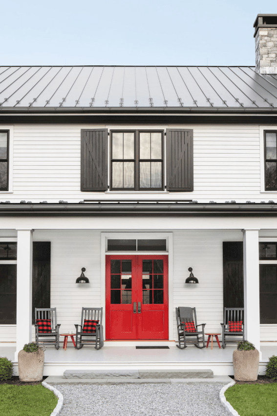 Very nice white farmhouse style of home with white exterior and red front door by chango & co.