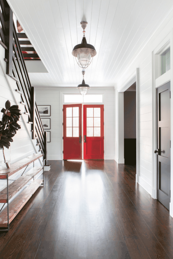 Farmhouse foyer featuring a hardwood flooring and white walls along with a red door. The pendant lights set on a white ceiling looks great too.