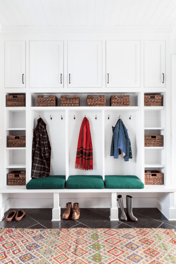 Close-up of custom built coat lockers in farmhouse style home.  Includes individual coat and bag cubbies, a long bench, shoe storage and more. Designed by chango & co.