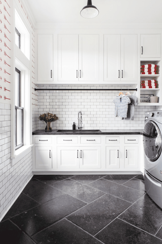Large white laundry room with custom cabinetry and sink. White subway tile backsplash. Designed by chango & co.