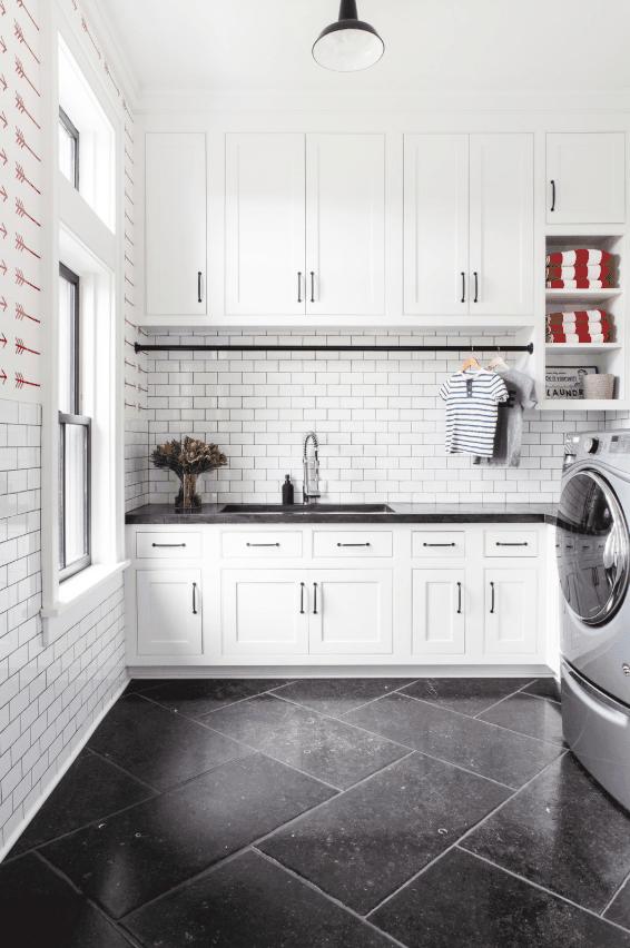 Large white laundry room with custom cabinetry and sink. White subway tile backsplash. Designed by chango & co.