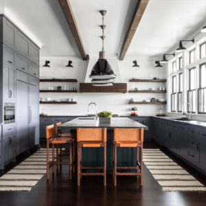 Spacious farmhouse kitchen with blue cabinetry, wood beams against white ceiling and rustic open-faced floating shelves by chango & co.