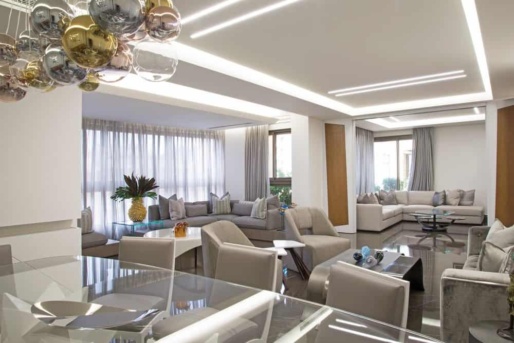 Living room with lots of couches and chairs in apartment designed by by Wael Farran Studio