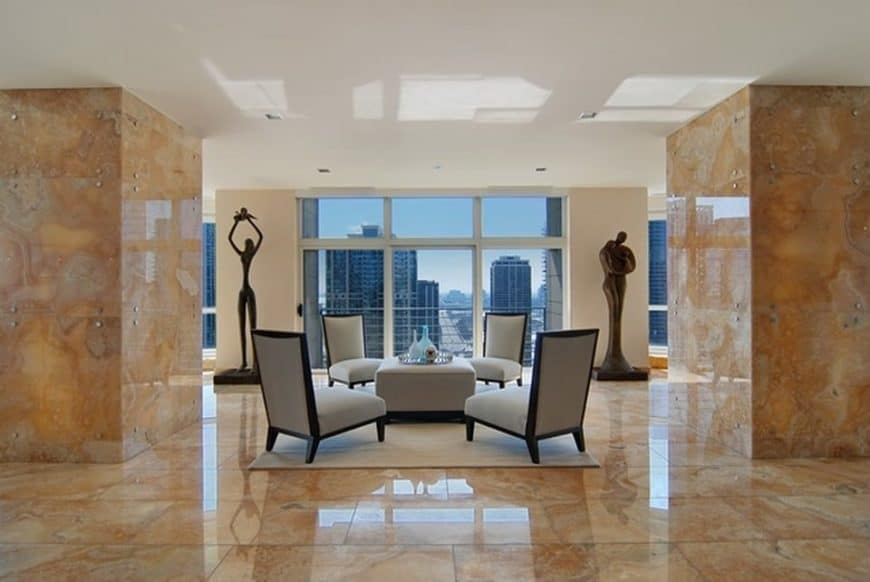This is a look at the living room and sitting area with gray chairs, beige marble floor and pillars adorned with a couple of statues. Image courtesy of Toptenrealestatedeals.com.