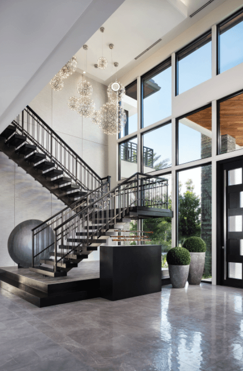 Modern foyer featuring a black floating staircase illuminated by luxurious glass ball chandeliers against the paneled glass walls.