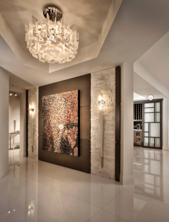 Fabulous foyer illuminated by a gorgeous chandelier that hung from a tray ceiling. It is designed with a huge canvas painting mounted on a wooden wall that's accented with bricks and vertical sconces.