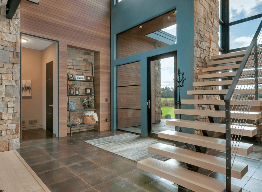 A glass front door fixed on the blue wall opens to this foyer that features shiplap walls accented with brick walls.