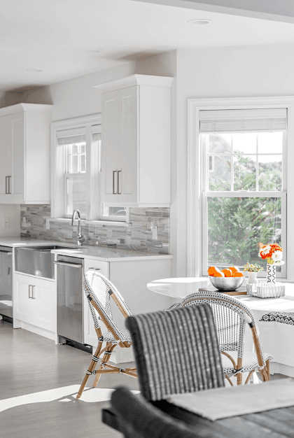 As expected, the kitchen is white with stainless steel appliances with a soft gray backsplash.