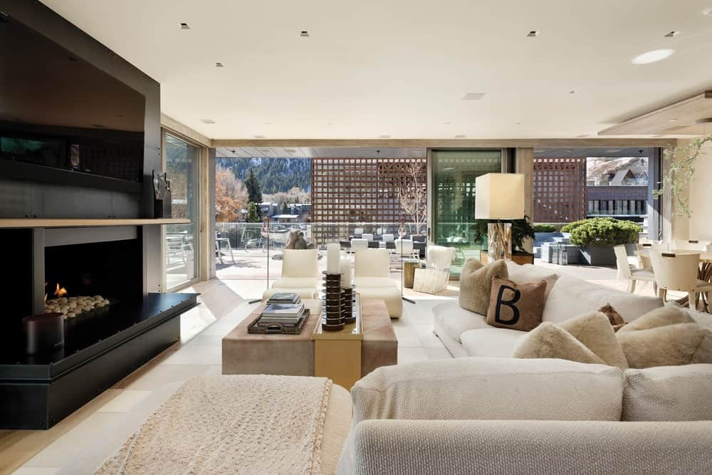 The living room has a large beige cushioned sofa facing a large contrasting black stone structure that houses the fireplace and the TV mounted above it. Image courtesy of Toptenrealestatedeals.com.