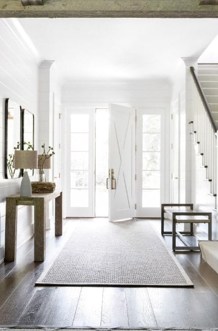 This bright farmhouse foyer features a hardwood flooring topped by a rug and a very bright white walls, doors and ceiling along with the staircase. This foyer looks so enchanting.