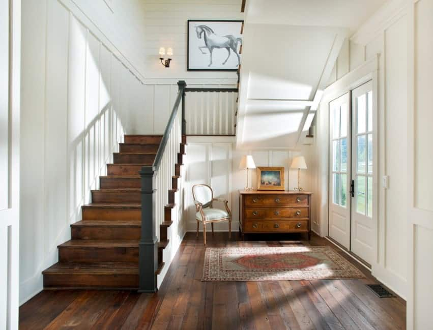 This farmhouse foyer features a hardwood flooring and white walls. The ceiling looks gorgeous.
