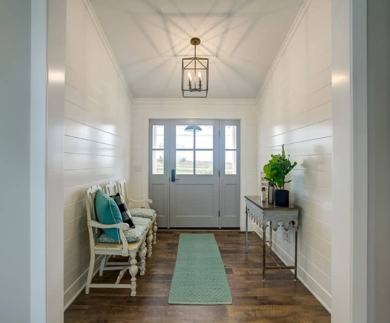 Farmhouse foyer featuring a hardwood flooring, green long rug and a small chandelier brightening the space.