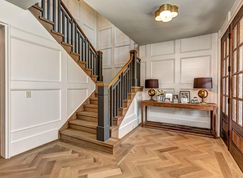 Farmhouse foyer boasting a stylish hardwood flooring and staircase steps with dark finished railings. The white walls fit well with the foyer's style.