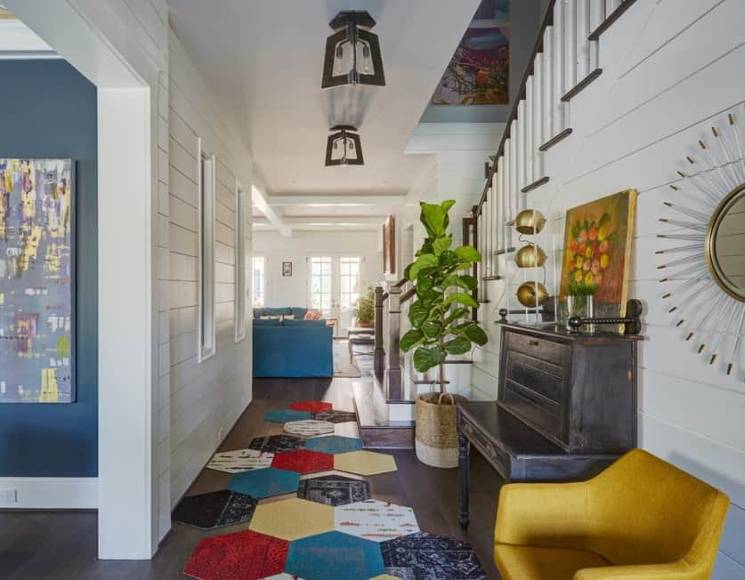 This farmhouse foyer features a colorful rugs and seats. The white walls mix well with the hardwood flooring and to the other details of the home.