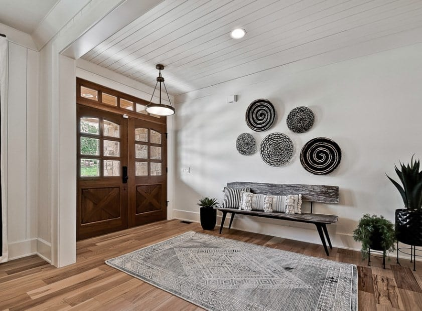 This farmhouse foyer boasts a hardwood flooring and white walls designed with a gray rug and black and white wall decors. The plants add colors to the room.