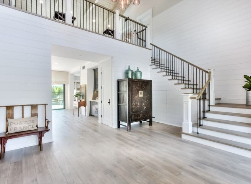 This large farmhouse foyer boasts a hardwood flooring and white walls and ceiling. The elegant chandelier set on the high ceiling brightens the staircase area.