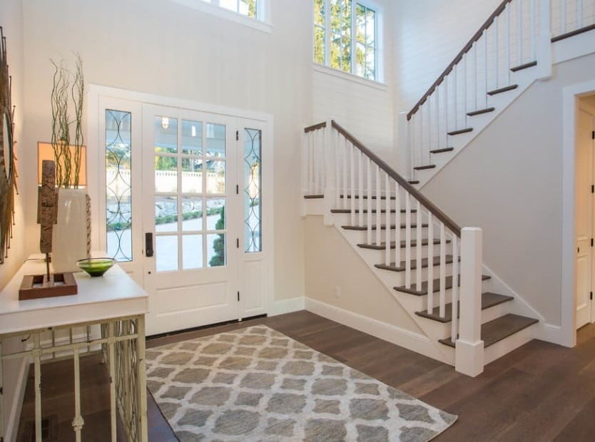 Farmhouse foyer with a hardwood flooring white walls and a perfect staircase matching the floors and walls.