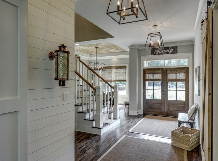 This farmhouse foyer features a hardwood flooring and light gray walls. The staircase looks perfectly placed.