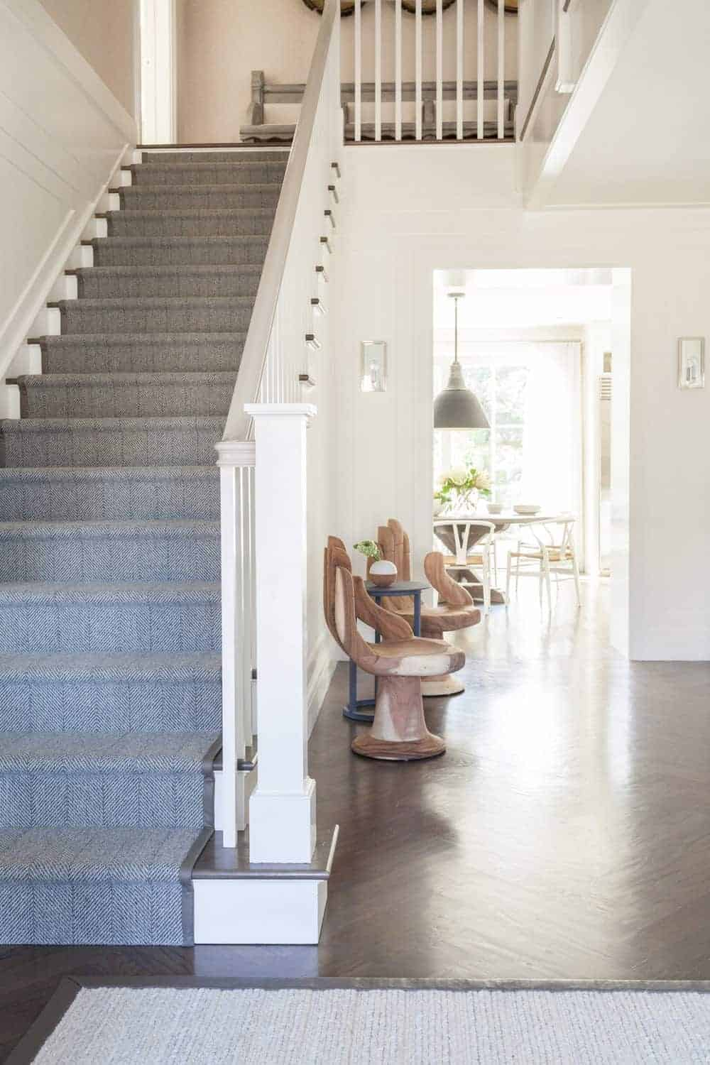 This elegant foyer is adorned with a couple of peculiar wooden chairs in the shape of hands. This gives an interesting welcome for the guests of this home that has a dark flooring contrasted by the white walls of the staircase.