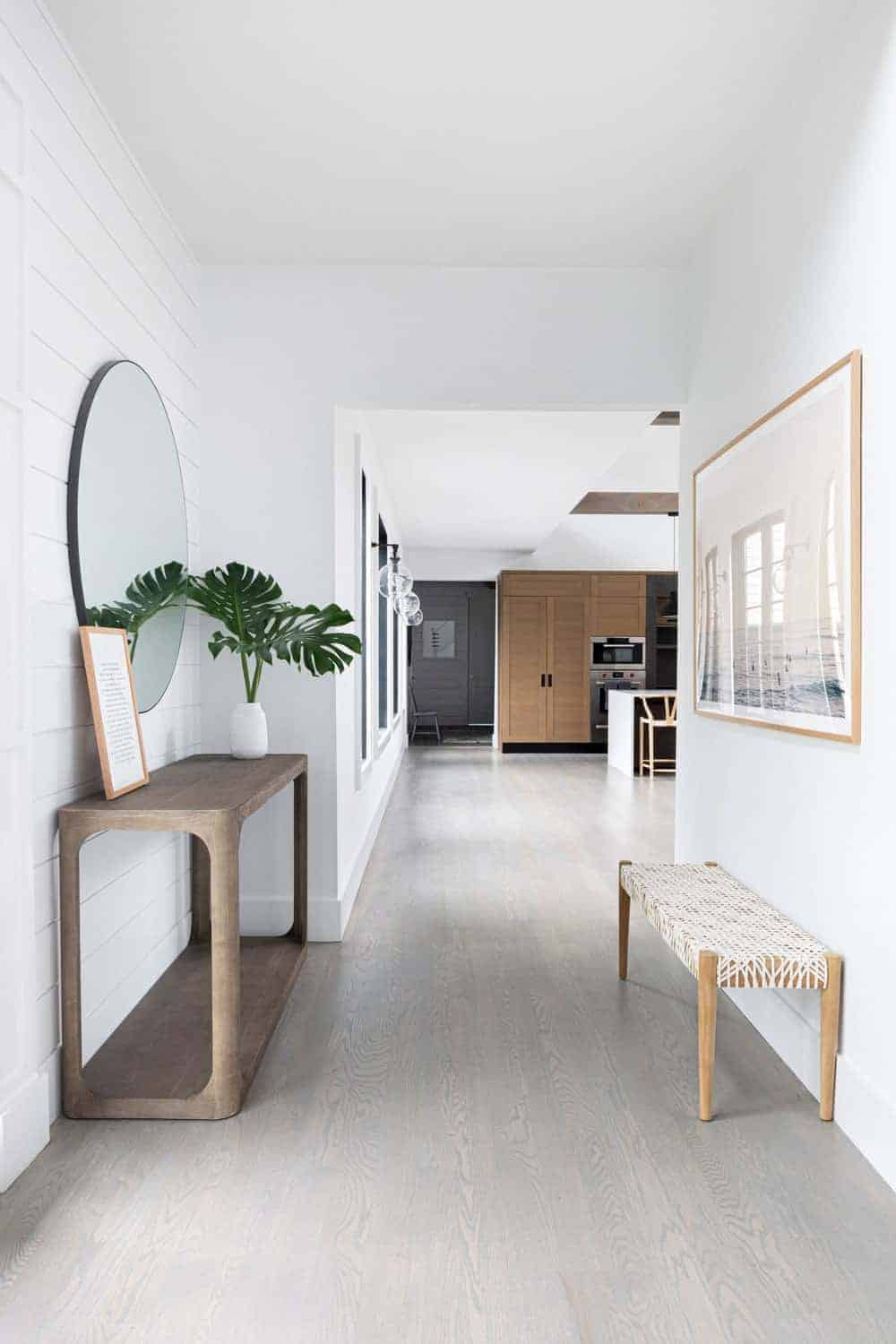 This is a hallway entry that has white walls in a plank finish complemented by a wooden console table bearing plant and a wall-mounted mirror above it. This can be enjoyed by those sitting on the wooden bench at the opposite wall.