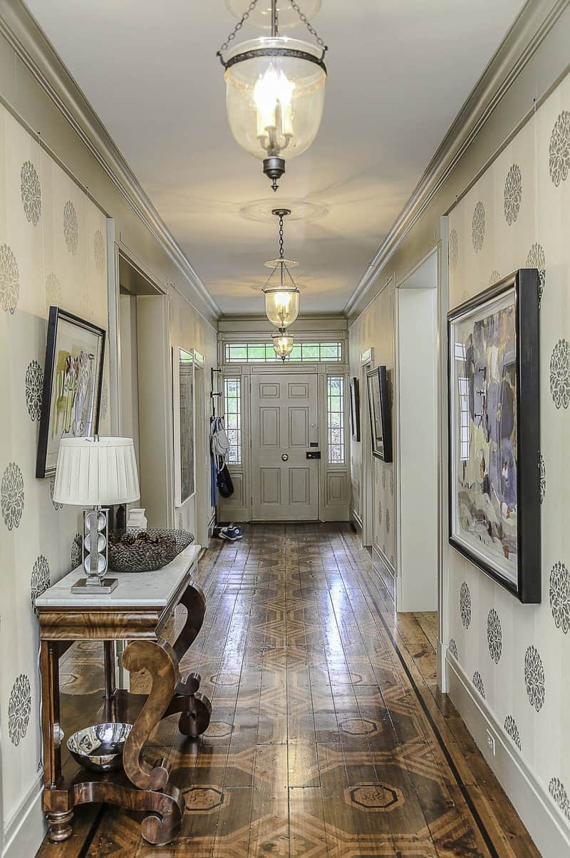 The hardwood plank flooring of this elegant foyer is marked with patterns that augment the hallway entrance. The wooden light gray main door has side lights and a transom window made of glass panels brightening the walls that are dominated by a wallpaper with patterns on it.