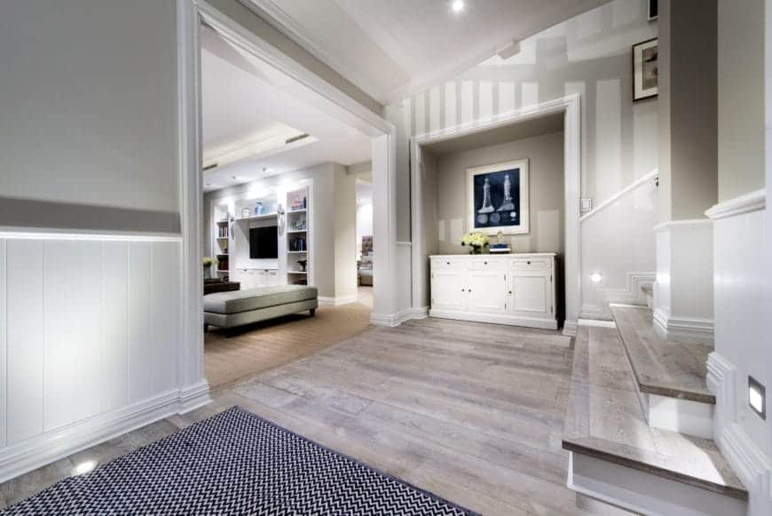 The simple patterned area rug marks the entrance to this simple Farmhouse-style foyer that has a hardwood flooring matching the steps of the stairs. This is complemented by the white walls and white shed ceiling with bright recessed lights.