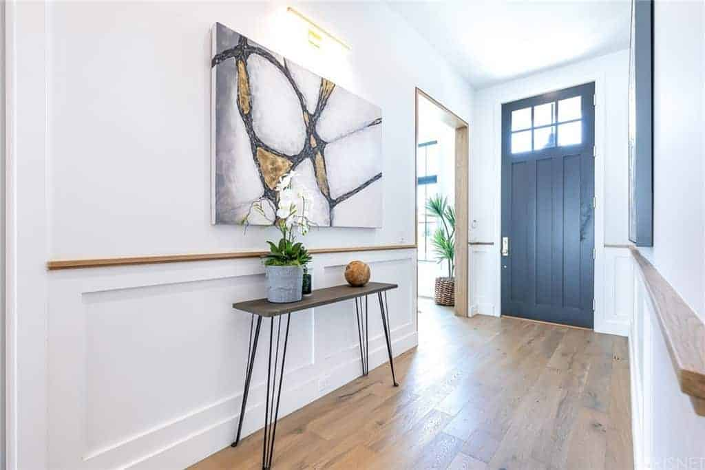 This bright white foyer is decorated with a simple wood-top console table with thin iron legs. It stands out against the white wooden finish of the wall that is accented with a colorful painting above. These are all illuminated by the transom windows of the door.