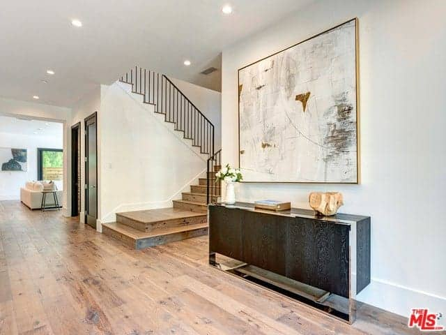 The white walls of this foyer is brightened by the recessed lights of the white ceiling. This is accented with a light hued abstract painting mounted above the dark wooden console table with a cabinet. This bears lovely decors and a flower vase.