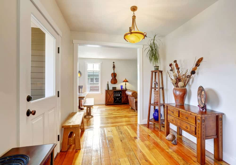 The white wooden main door matches with the white walls contrasted by the hardwood flooring. This blends with the console table, wooden bench and the decorative shelving in the corner that bears vases and a potted plant on top.