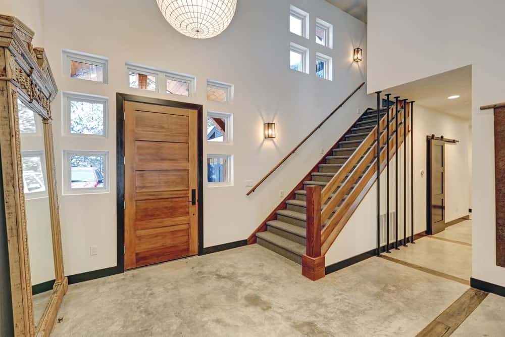 The white walls surrounding the wooden main door has small windows on it that acts as the door's side lights and transom window. This door is flanked on the right side by the stairs with wooden rails and the left side is a larg mirror leaning on the wall.