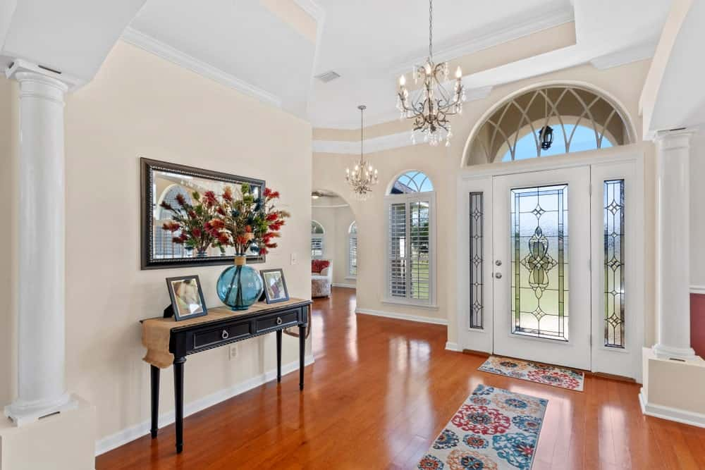 The redwood flooring is brightened up by the frosted glass panels of the main door that has side lights and an arched transom window. This redwood flooring is topped with a colorful floral area rug topped with a majestic and elegant chandelier from the white ceiling.