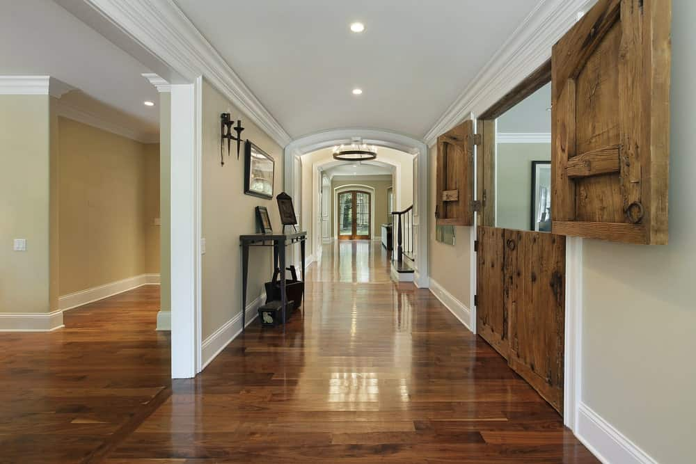 The simple foyer has sleek and shiny hardwood flooring that matches with the door on the right that has a distinctive Farmhouse-style design. This door stands out against the light gray walls and the white ceiling that has recessed lights.