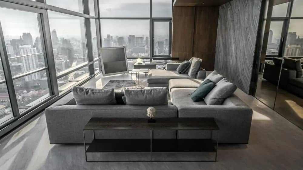 This is a look at the bright and airy living room of the apartment with a set of gray sectional sofas brightened by the tall glass walls that also showcase the skyline view of the city below. Designed by ONG&ONG.