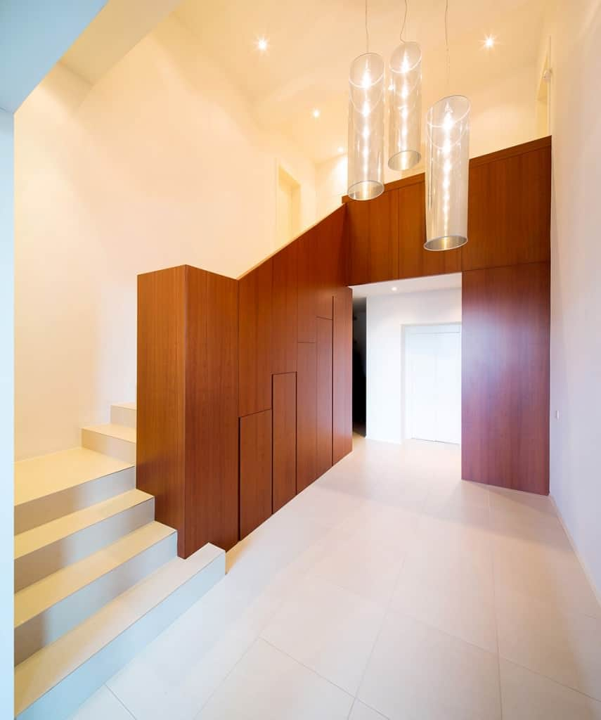 This foyer is full of luster and shine. Although no decorative item is used, the trio of long cylindrical lights in the centre of the place and the fascinating use of a wooden wall makes this foyer stand out.