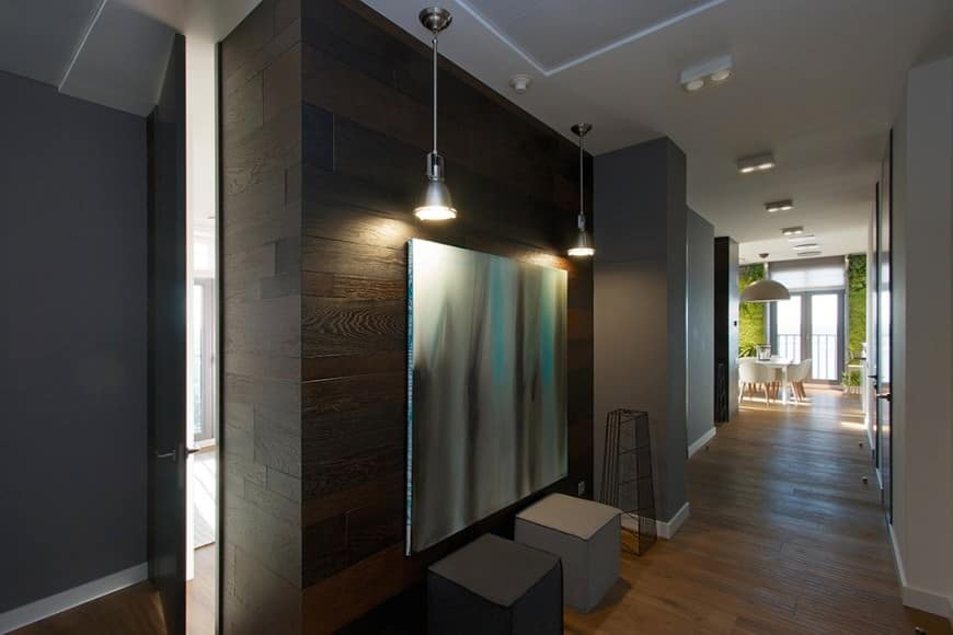 This foyer makes a dramatic use of lighting. The hallway is kept dark with dim lights and a deep black-brown wooden wall. The abstract painting accentuated by the hanging lamps and the cube-shaped seats add an artistic touch.