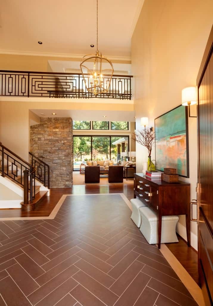 This foyer redefines the idea of a rug. Instead of runners, it 'carpets' the entrance with a zigzag mosaic tiled floor that matches the chestnut furniture and railings. Wall-length windows opposing the foyer provide a brilliant view of the lush scenery outside and give the place a more open look.