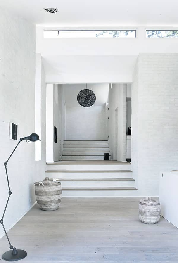 This monochromatic foyer seems like the ideal design for studio apartments. Jute chenille baskets, a sleek and slender metallic lamp and a round hanging light make great adornments to a bare space.