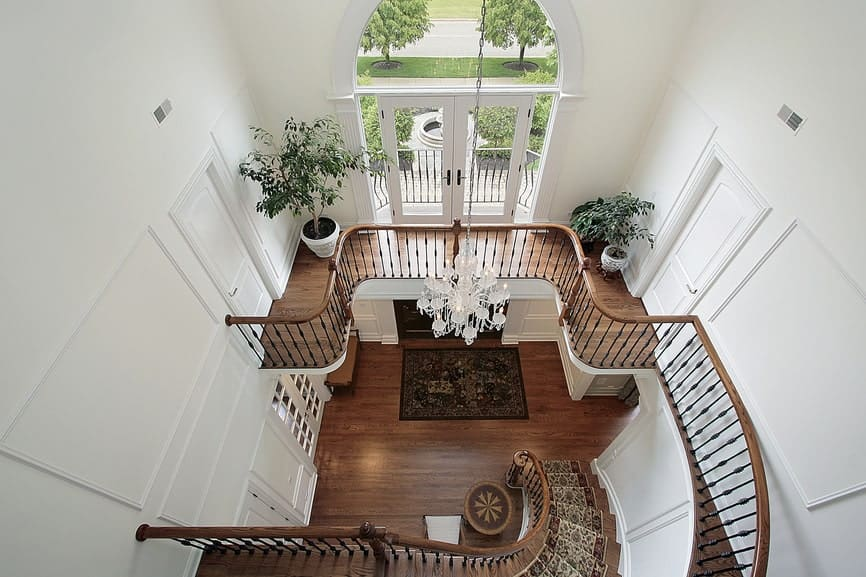 The white crystal chandelier hanging over the dark patterned area rug of the foyer matches well with the bright white walls brightened by the second floor glass doors. These bright elements are balanced by the dark brown hardwood flooring as well as the wrought iron railings of the stairs extending to the second floor.