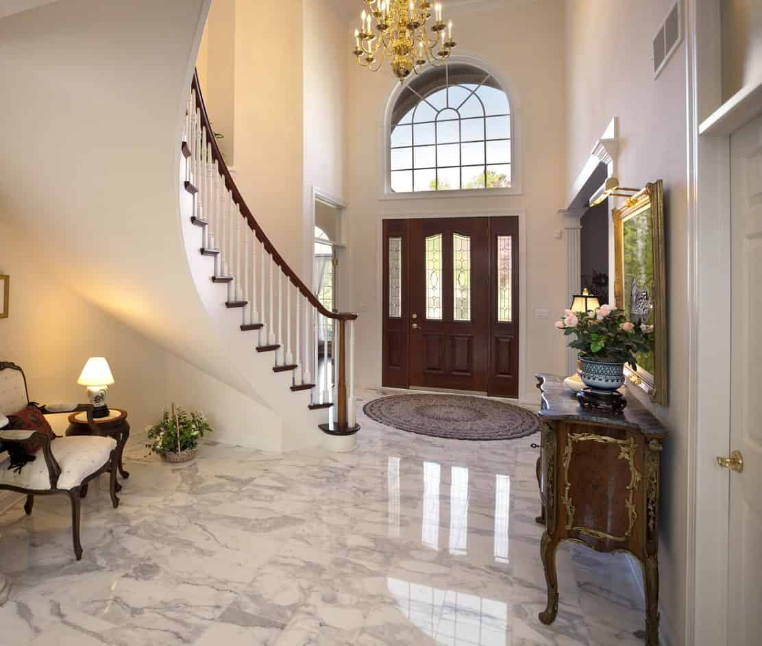 This gorgeous foyer has a dark wooden main door with side lights that stand out against the light beige walls and tall ceiling that is dominated by a large golden chandelier. This is complemented by a large arched transom window that brings in natural lights to the white marble flooring.