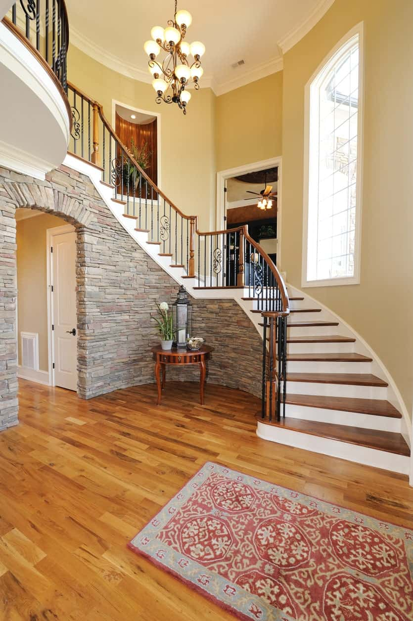 The textured gray stone walls of this foyer works well with the hardwood flooring that is topped with a red patterned area rug for a welcome mat. The stone wall follows the curvature of the staircase and is adorned with a small wooden table bearing a lamp and decors.
