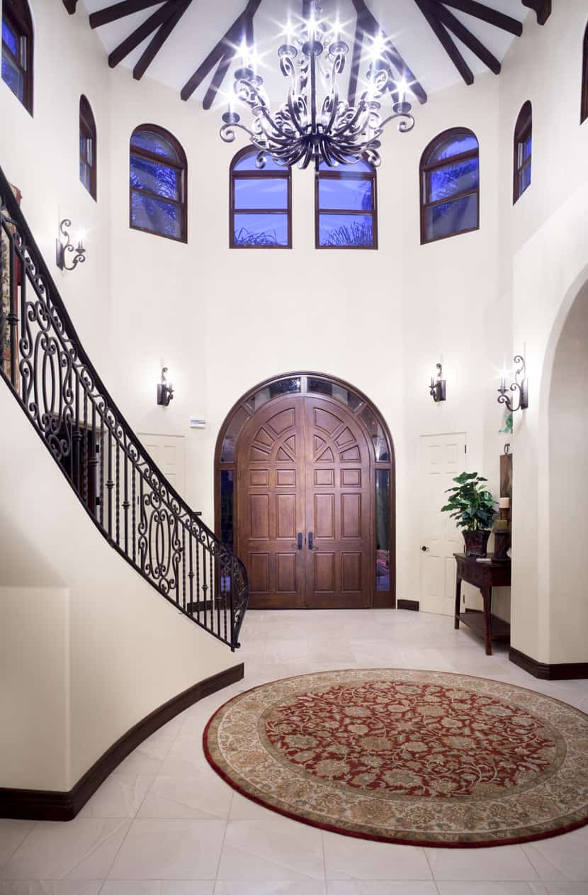 Best for houses with a high-rise ceiling, this foyer speaks of beauty and sophistication. Vintage-style light fixtures with a magnificent chandelier coupled with indigo glass windows against crème-colored walls form the perfect entrance to a grand house.