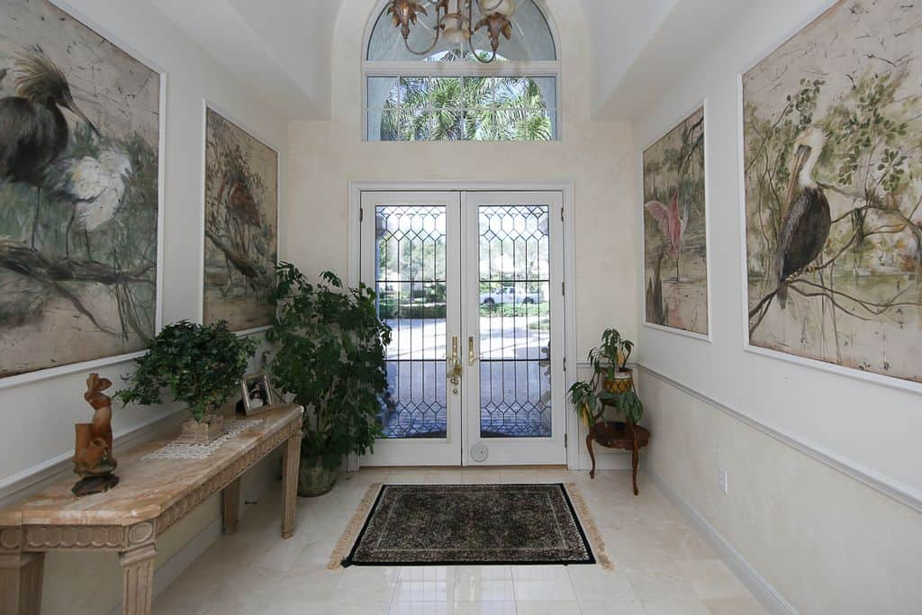Simple yet lively best describe this entrance. Lots of indoor plants that complement the paintings of wild birds and the marble foyer table at the side make this a homely entryway.