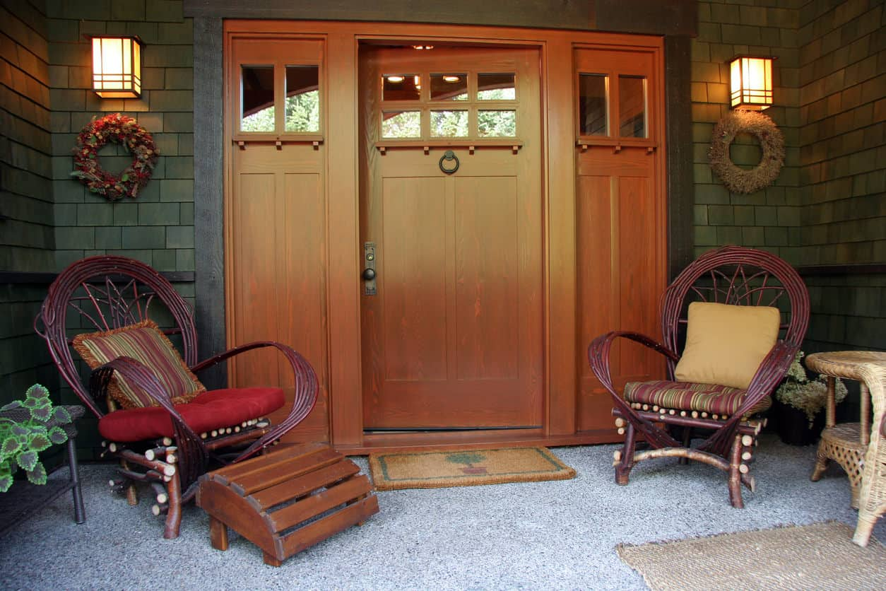 This is an example of a very simple porch with two chairs at the entrance, flower wreaths on both sides and rugs and mats on the floor.