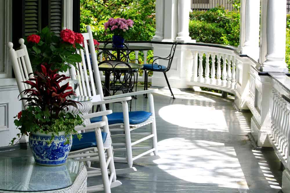 If you are looking for an almost ostentatious porch, this is the one for you. It has a classic white theme throughout, with colored chairs and fancy flowers on a glass top table.